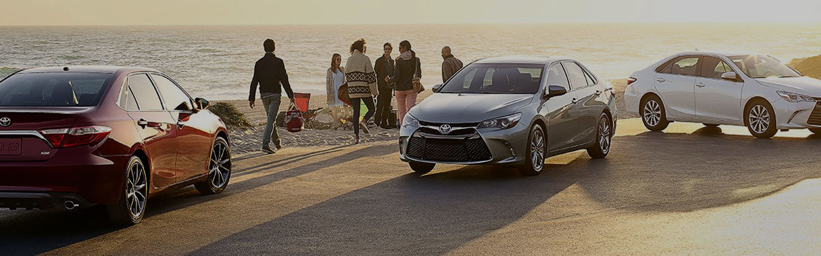 Toyotas and young people at the beach.